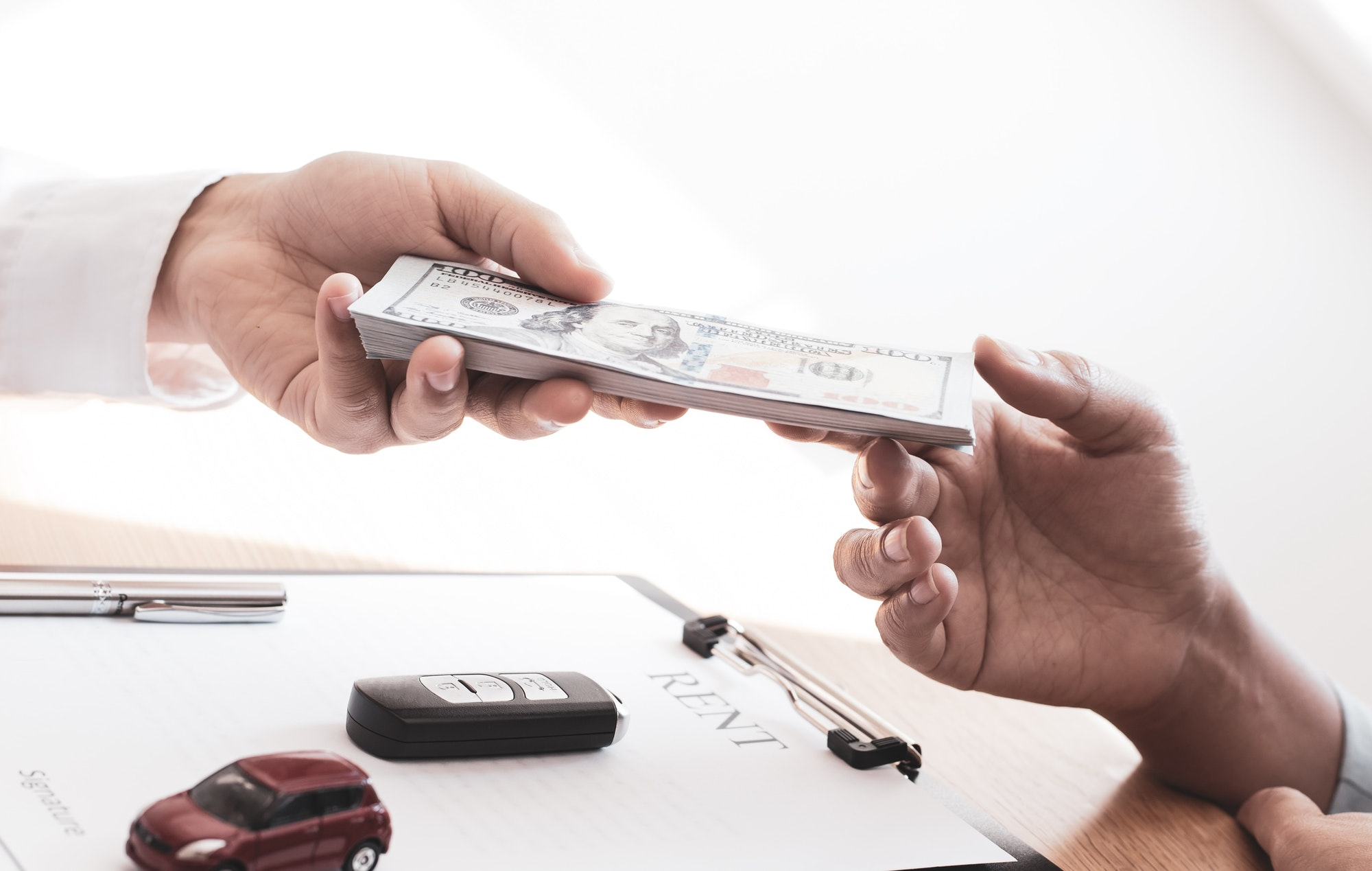 The car salesman handed the keys to the customer who passed the car purchase loan conditions