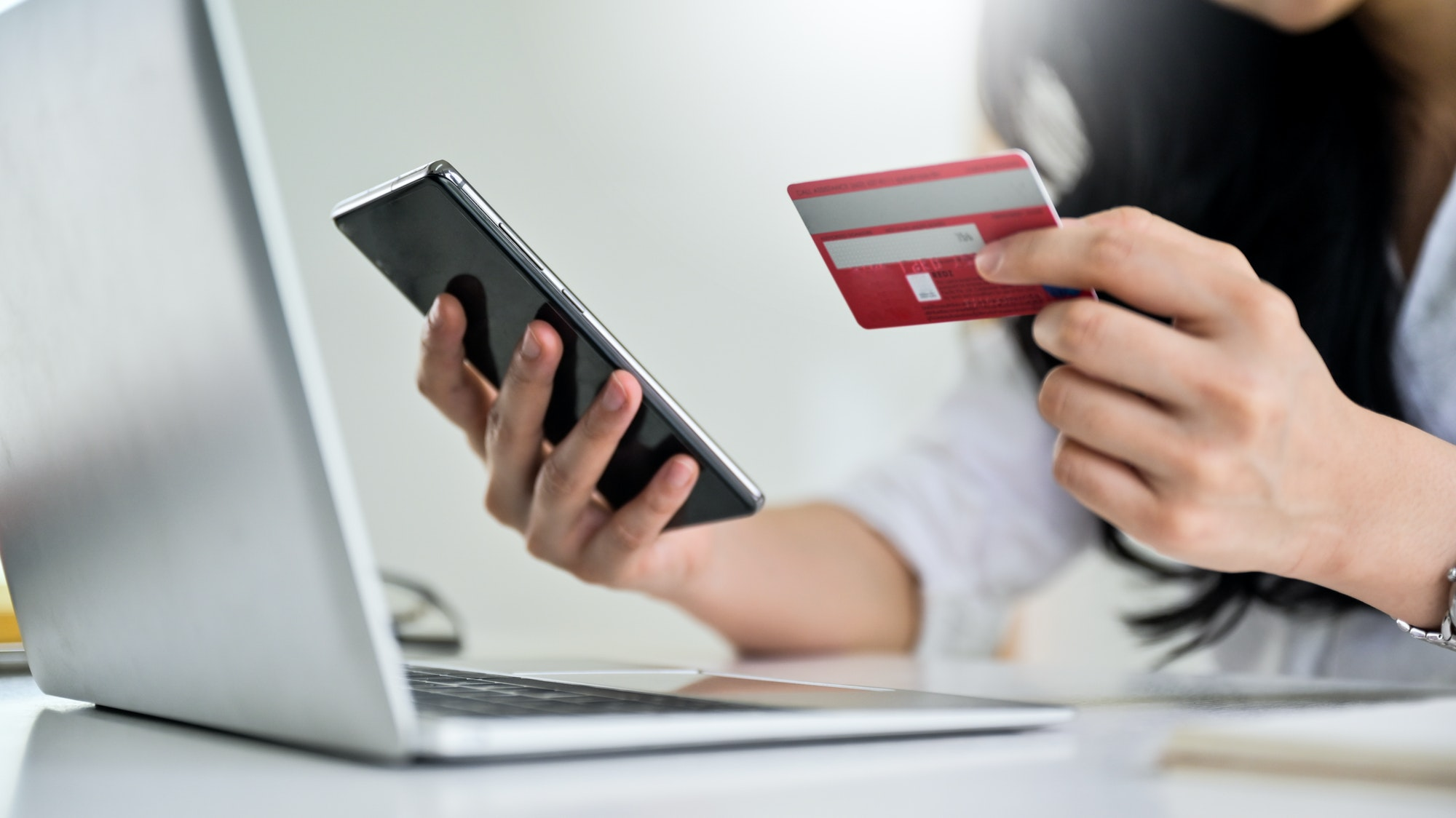 Young woman holding credit card and smartphone with laptop, Credit card payment.